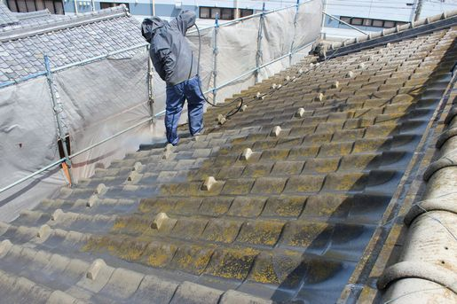 瓦屋根を塗装するお客様の家